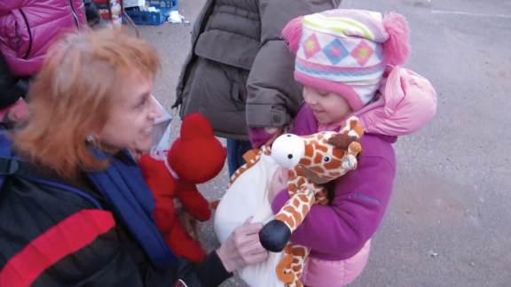 Dr. Judy giving SI child a stuffed toy for comfort